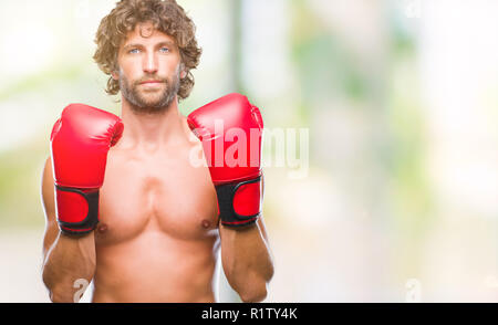 Handsome hispanic boxer man wearing boxing gloves over isolated background with serious expression on face. Simple and natural looking at the camera. - Stock Photo