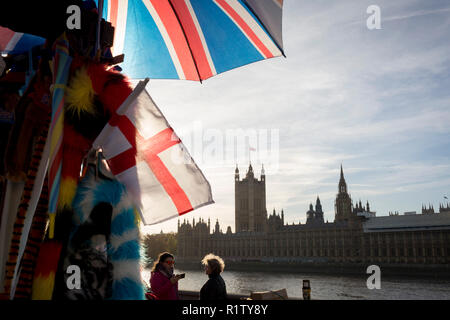 On the day that Prime Minister Theresa May petitions her cabinet on the current negotiations to leave the EU, the UK and English flags hang at a tourist souvenir stall opposite the Houses of Parlament on the river Thames, on 14th November 2018, in London, England. - Stock Photo
