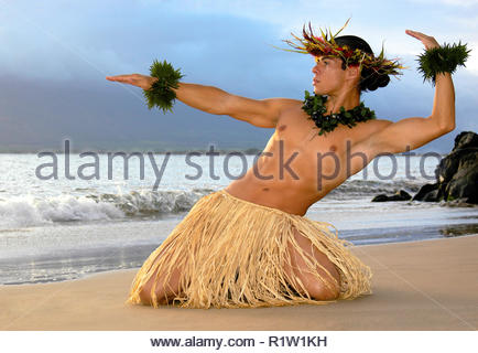 Male hula dancer performs on the beach as the sun sets. - Stock Photo