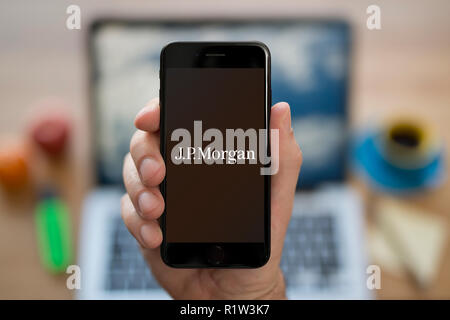 A man looks at his iPhone which displays the JP Morgan logo, while sat at his computer desk (Editorial use only). - Stock Photo