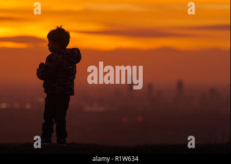 A four year old boy looks over Manchester City Centre in the distance at sunset taken from the Pennine village of Mossley on Wednesday 14th November 2 - Stock Photo