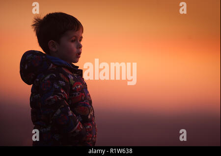 A four year old boy looks out from the top of a hill at sunset taken from the Pennine village of Mossley on Wednesday 14th November 2018. - Stock Photo