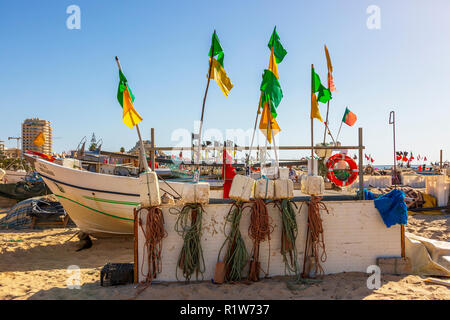 LOcal fishing boat on the beach with the fishing floats and flags drying in the evening sun, Monte Gordo, Algarve, Portugal - Stock Photo