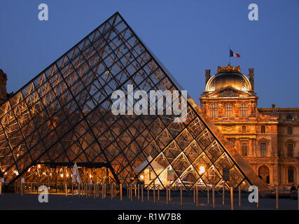 The Palais du Louvre: the Pyramid in the centre of the Cour Napoleon, illuminated at dusk - Stock Photo