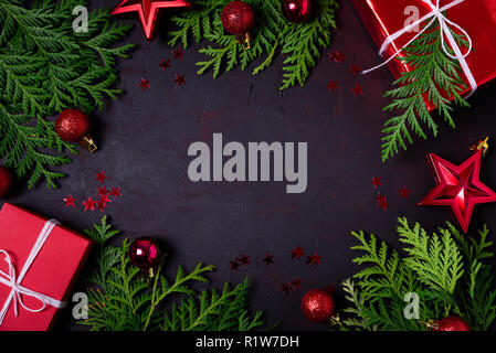 Christmas frame of red gift boxes, fir branches, confetti and toys on black background. Flat lay. Top view. Copy space - Stock Photo