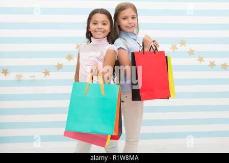 birthday presents. small happy girls or school kids with birthday presents. small happy girls with shopping bags on school market. go shopping. Best discounts and promo codes - Stock Photo