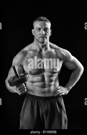 Always in good shape.Strength and motivation.Sportsman or man with athletic torso hold roller slide gym equipment. Training and workout in gym, black and white. man - Stock Photo