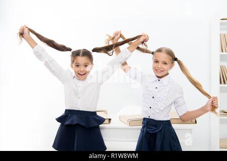 Happy little girls play hairdresser game at school. Little children girls do hair as hairdresser. - Stock Photo
