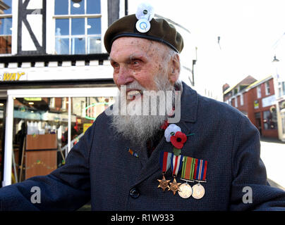 World War Two veteran George Evans aged 95 wearing red poppy and white peace poppy with his Quakers badge on beret at Remembrance Service a Parade in  - Stock Photo