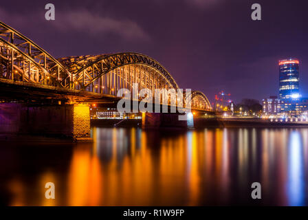 View of the Hohenzollern Bridge, the Skyscraper Cologne Triangle, the Hyatt Regency and the Long River Rhine at Night in Germany Cologne 2018. - Stock Photo