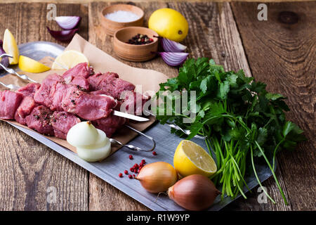 Raw fresh beef skewers,butchery uncooked chopped meat and cooking ingredients on wooden table - Stock Photo