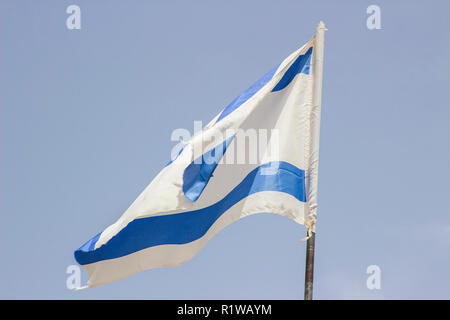 A tattered Israeli Flage aloft in a stiff breeze against a blue sky at the Banais Nature Reserve in the Golan Heights Israel. - Stock Photo