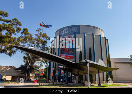 Plane heading towards San Diego airport passing behind the San Diego Air & Space Museum, Balboa Park, San Diego, California, United States. - Stock Photo