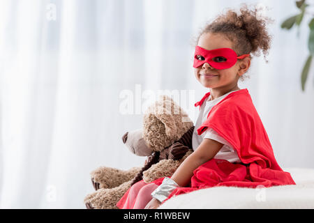 Adorable little african american child in superhero costume and mask with teddy bear smiling at camera