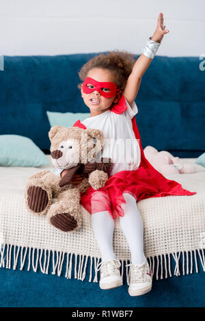 Adorable little african american child in superhero costume sitting on bed with teddy bear