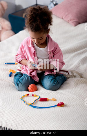 Curly african american kid playing with toy stethoscope on the bed - Stock Photo