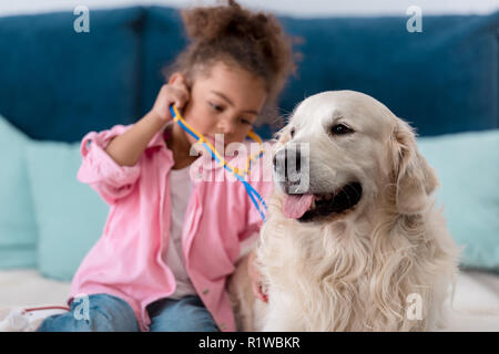Adorable african american kid playing  with stethoscope and her retriever - Stock Photo