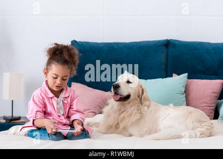 Curly african american kid sitting on the bed with retriever and looking in smartphone - Stock Photo