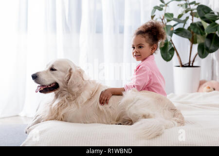 Adorable african american kid hugs her dog on the bed - Stock Photo