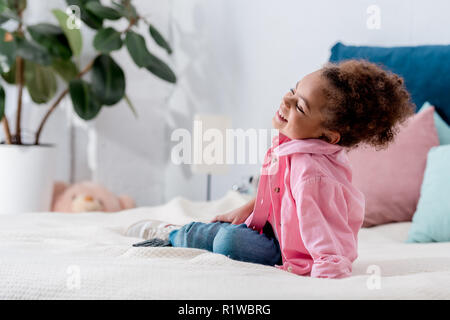 Curly African american kid sitting on the bed and smiling - Stock Photo