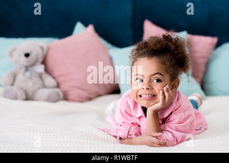 Adorable curly African american kid lying on the bed and smiling - Stock Photo