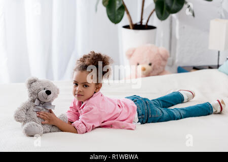 Curly african american kid lying on the bed with her teddy bear - Stock Photo