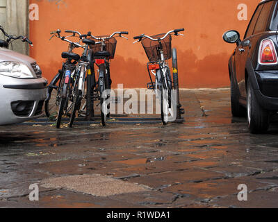 orange wall gives dramatic background to four parked bicycles in a bike rack between two cars on a wet pavement in Florence,Tuscany,Italy - Stock Photo