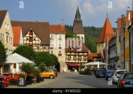 Medieval gate of the tower, church St. Lorenz at the back, brick tower or Allioturm on the right, Pettenkoferplatz, Berching - Stock Photo
