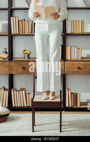 close up of adult woman standing on chair in living room and reading book - Stock Photo
