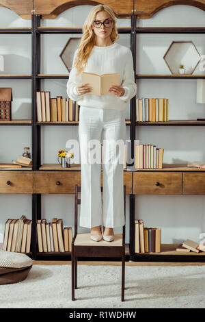 adult woman in glasses standing on chair in living room and reading book - Stock Photo