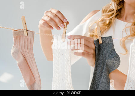 close up of woman putting socks on clothesline with clothespins - Stock Photo