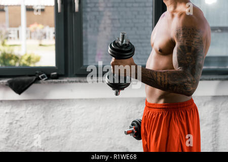 cropped image of muscular shirtless african american sportsman exercising with dumbbells at gym - Stock Photo
