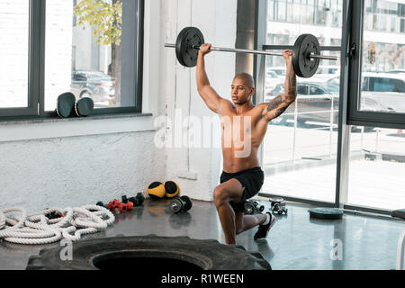 muscular bare-chested young sportsman lifting barbell and looking away in gym - Stock Photo
