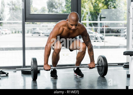 muscular bare-chested young african american man lifting barbell in gym - Stock Photo
