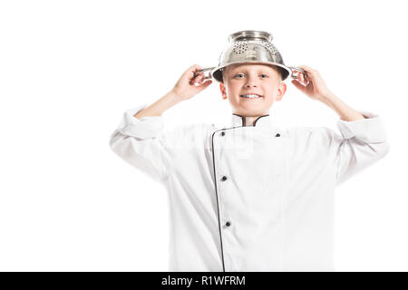 portrait of preteen boy in white chef uniform with colander on head isolated on white - Stock Photo
