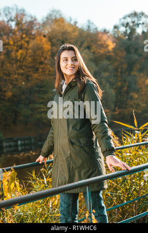 low angle view of happy young woman in jacket and yellow rubber boots posing near railing outdoors - Stock Photo