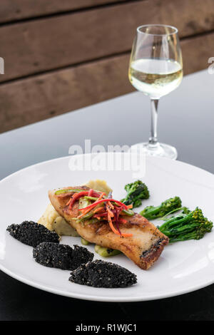 red snapper fish fillet with vegetables and black rice with black sesame seeds asian modern fusion dish in melbourne australia restaurant - Stock Photo