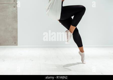 Partial view of female doing antigravity yoga in studio - Stock Photo