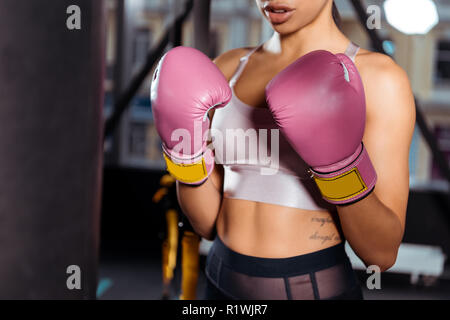 Partial view of strong girl in boxing gloves practicing boxing in gym - Stock Photo