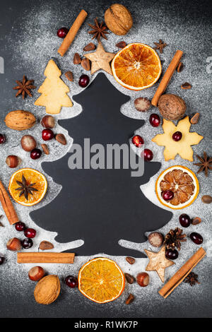 Shape of Christmas tree made from icing sugar on dark background with nuts, cranberries, star anise, pine nuts, cookies and dry slices of orange Stock Photo