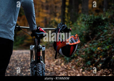 Man pushes his mountain bike through a forest - Stock Photo