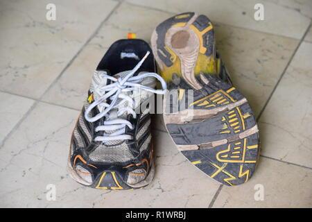 Pair of old Run and walking shoes worn out and with holes under the sole. Paar alte Lauf- und Wanderschuhe abgenutzt und mit Löchern unter der Sohle - Stock Photo
