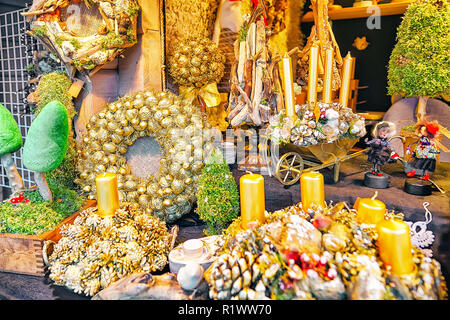 Riga, Latvia - December 25, 2015: Stall with golden festive wreaths at the Christmas market in winter Riga in Latvia. - Stock Photo