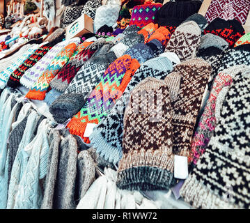 Warm colorful mittens, gloves, socks and hats at one of the stalls at the Christmas market in winter Riga in Latvia. - Stock Photo