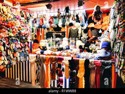 Warm colorful mittens, gloves, socks and hats at one of the stalls at the street Christmas market in winter Riga in Latvia. - Stock Photo