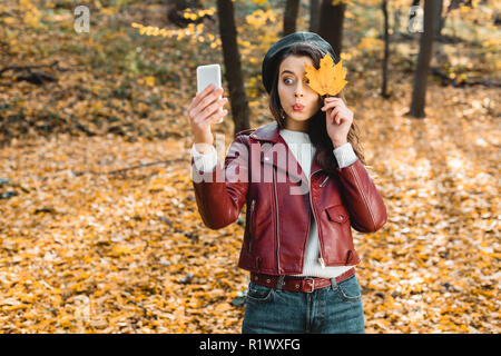 fashionable girl doing grimace and taking selfie with yellow leaf on smartphone in park - Stock Photo