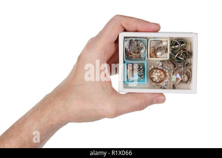 An elderly man holds in his hand a cardboard box with his old  wife's  jewelry. Mass production. Isolated on white studio macro - Stock Photo