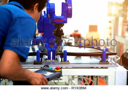 Industrial robot welding automotive part in car factory - Stock Photo