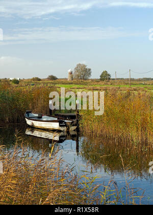 Boats moored in the narrow cut of West Somerton staithe, a remote part of the Norfolk Broads accessed via the River Thurne and Martham Broad. - Stock Photo
