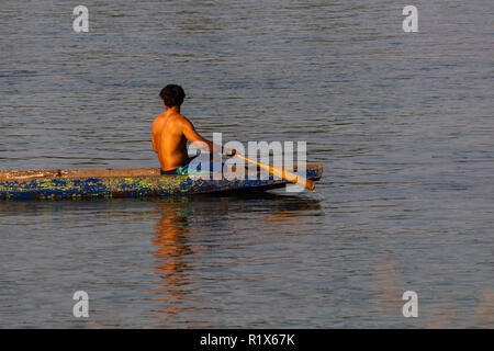 Don Det, Laos - April 22, 2018: Local man rowing a wooden long boat over the Mekong river in southern Laos - Stock Photo